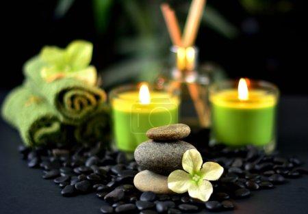 Photo pour Pierres de spa et rochers avec bougies allumées, serviettes, fleurs et parfum sur fond noir - image libre de droit