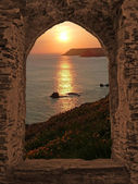 View through arched castle window to sunset coastal landscape, cornwall