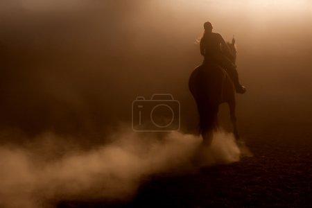 Photo pour Équitation dans la poussière avec rétro-éclairage - image libre de droit