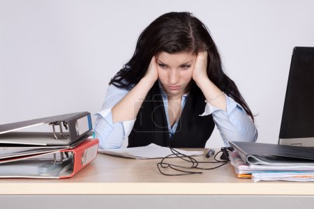 Young female office worker at desk