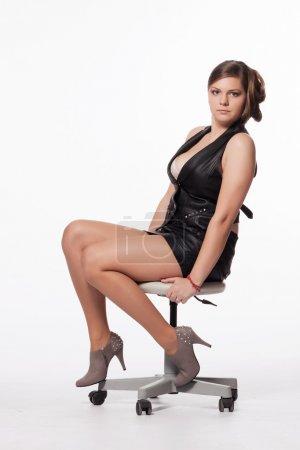 Photo pour Jeune femme en veste de cuir, mini-jupe, talons hauts, avec coupe de cheveux exceptionnelle, assis sur une chaise pivotante - image libre de droit