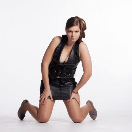 Photo pour Jeune femme en veste de cuir, mini-jupe, talons hauts, avec coiffure exceptionnelle à genoux sur le sol - image libre de droit