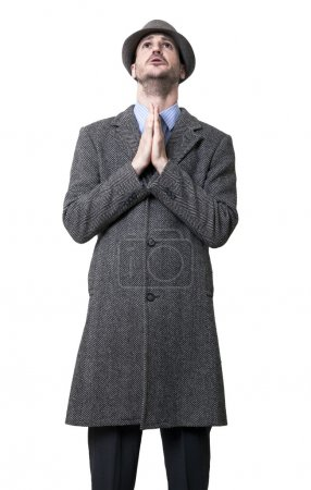 Photo for A young adult malewearing a gray overcoat and hat. He is looking upwards with a pleas in his eyes, his hands put together in a pleading gesture. Isolated on white background. - Royalty Free Image