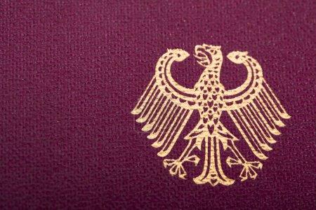 Photo pour Un coup de macro de l'écusson allemand imprimé sur une couverture de passeport allemand - image libre de droit