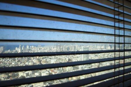 Photo pour Stores vénitiens défocalisés dans leur position ouverte, révélant une fenêtre sale avec des bâtiments de tel-aviv et la mer Méditerranée en arrière-plan. - image libre de droit
