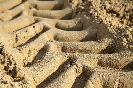 Photo pour Un gros plan des traces de pneus de tracteur sur le sable de plage. Profondeur de champ faible . - image libre de droit