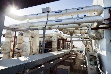 Photo pour Ce système complexe de tuyaux et de vannes est situé sur le toit d'un immeuble de bureaux et fait partie du système d'alimentation en eau de la climatisation commerciale CVC du bâtiment. . - image libre de droit