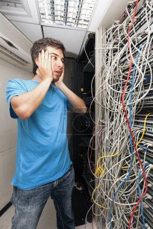 Photo pour Homme adulte dans son 30 début la recherche avec horreur sur le chaos de câbles emmêlés sur le serveur en face de lui. administrateur réseau pauvres. - image libre de droit