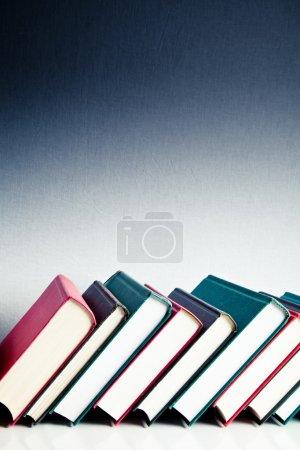 Photo pour Livres rouges, noirs et verts en rangée sur une surface réfléchissante blanche - image libre de droit