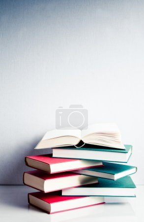 Photo for Blank open book on a green and red stack of books in balance - Royalty Free Image