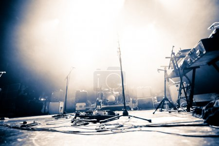 Photo pour Scène éclairée vide avec batterie, guitare et micros - image libre de droit