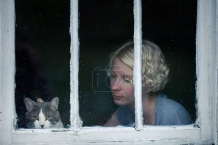 Woman and Cat Looking at the Rainy Weather By the Window