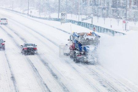 Photo pour Camion chasse-neige, enlever la neige de l'autoroute pendant une tempête de neige froide journée d'hiver - image libre de droit