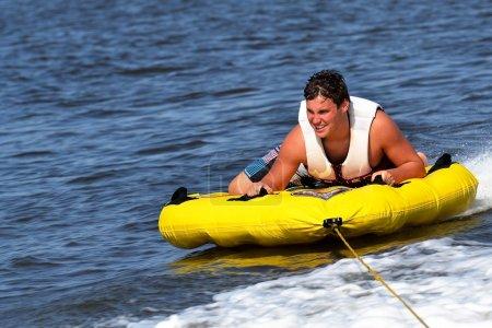 Teenage Tuber Sliding Across the Water