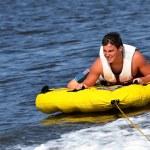 Teenager sliding across boat wake in inner tube sc...