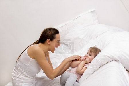 Mother and daughter playing on the bed