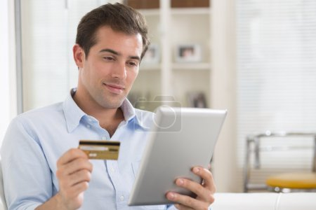 Photo for Young male shopping online on his digital tablet PC in his living room - Royalty Free Image
