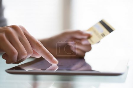 Woman shopping using tablet pc and credit card .indoor.close-up