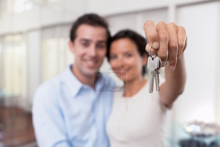Happy smiling young couple showing a keys of their new house