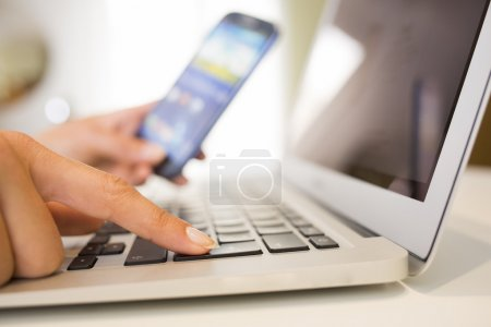 Woman hands with smart phone and computer keyboard