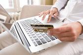 Zblízka ženské ruce držící kreditní kartu a používat počítač