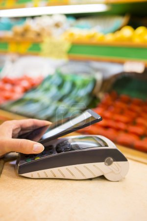 Woman paying with nfc technology on mobile phone, shopping, supe