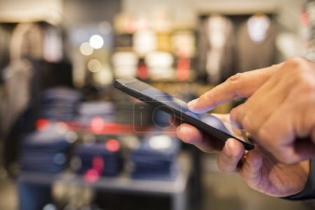 Close up of a man using mobile phone in clothing store