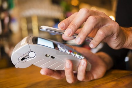 Man paying with NFC technology on mobile phone, in restaurant, b