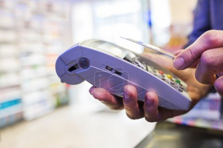 Man paying with NFC technology on credit card, in pharmacy