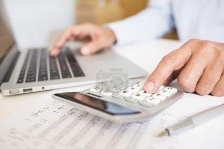 Photo pour Main mâle ordinateur portable ordinateur calculatrice argent stylo - image libre de droit