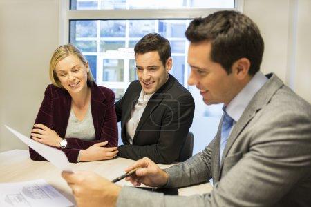 Photo pour Couple réunion agent immobilier pour acheter une propriété - image libre de droit