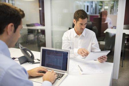 Photo pour Deux hommes d'affaires travaillant dans le bureau avec ordinateur portable et tablette PC - image libre de droit