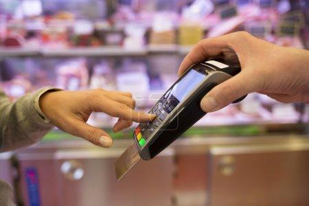 Photo pour Femme main avec carte de crédit entrant mot de passe sur le terminal POS dans le supermarché - image libre de droit