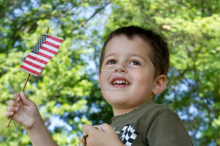 Photo for A cute brown-haired, brown-eyed little boy waving an American flag and smiling - Royalty Free Image
