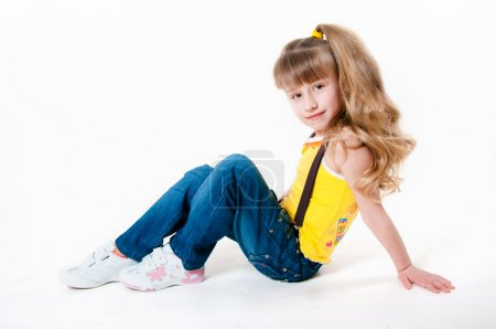 Little girl in jeans on a white background