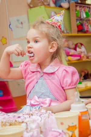 Photo pour Petite fille manger du gâteau sur sa fête d'anniversaire - image libre de droit