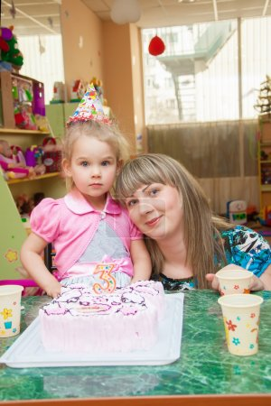 Little girl with her mother with a birthday cake o...