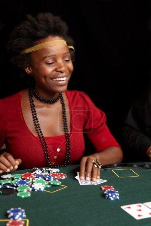 Photo pour Femme africaine jouant aux cartes, jetons et joueurs jouant autour d'une table de poker en feutre vert. Profondeur de champ faible - image libre de droit