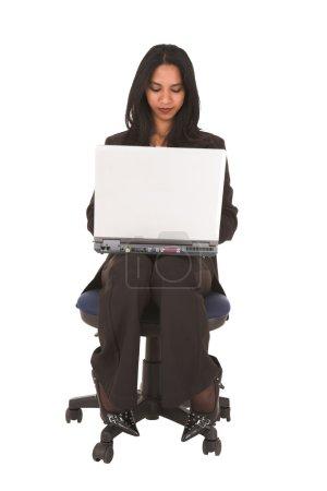 Photo pour Jeune femme d'affaires afro-indienne adulte assise avec un ordinateur portable sur ses genoux sur un fond blanc . - image libre de droit