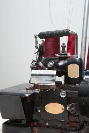 Old industrial overlocking machine in sewing factory