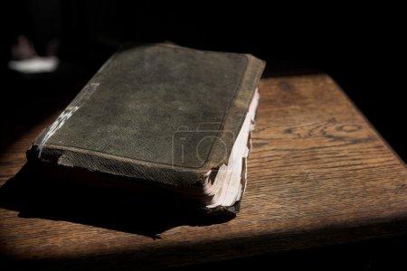 Photo pour Vieille bible recouverte de cuir couchée sur une table en bois dans un rayon de soleil (pas une image isolée) Profondeur de champ peu profonde. Focus sur le bord le plus proche de la Bible - image libre de droit