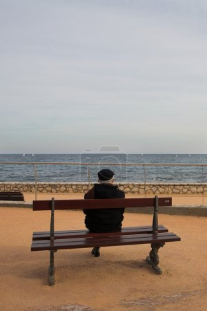Lonely man on Bench, next to the sea