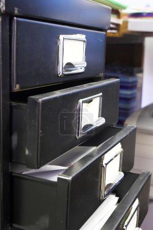 Nahaufnahme eines schwarzen Mini-Aktenschranks und Etiketts mit vier offenen Schubladen