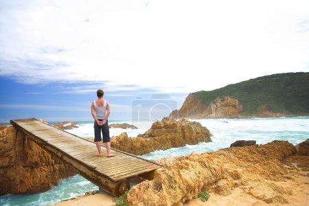 Woman facing the sea standing on a bridge