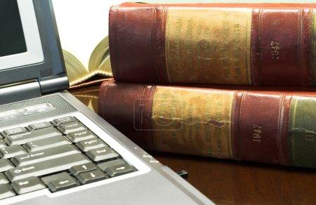 Photo pour Ordinateur portable et livres juridiques sur la table - image libre de droit