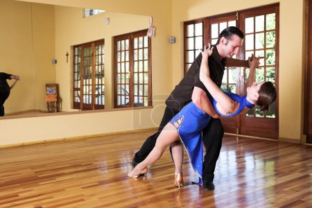 Photo for A young adult couple dancing and practicing ballroom dancing together in a studio - Focus on woman - Royalty Free Image