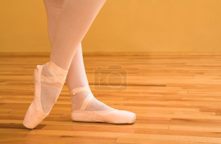 Woman pointing with ballet shoes.