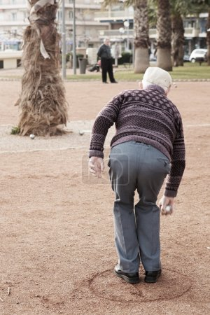 An old man playing petanque in Antibes, France