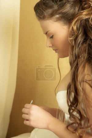 Woman in underwear sitting on a bed. Looking down.
