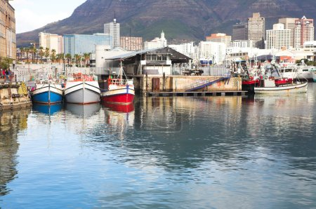 Cape Town waterfront harbor with three boats reflecting in the water and the City skyline in the background.